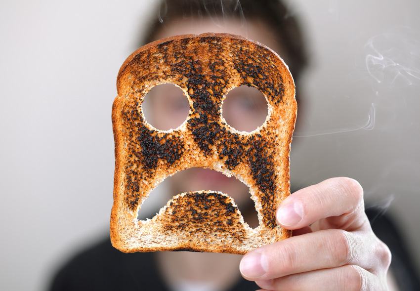 Man holding up a burnt slice of toast with an unhappy smiley conept for bad start to the day